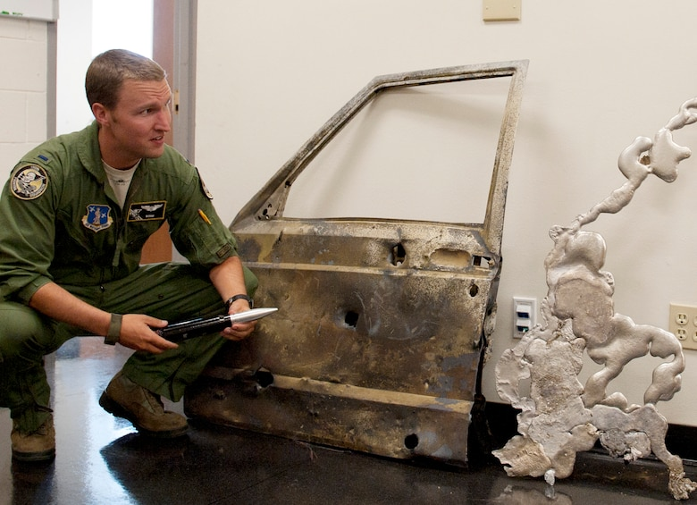 1st Lt. Tom Silkowski, A-10 Pilot with the 190th Fighter Squadron, examines the door and melted engine block from a vehicle destroyed during a strafe training mission at Saylor Creek Range August 21. The targets were moving as fast as 40 miles an hour while pilots took aim, disabled, and destroyed the remote controlled vehicles. This type of strafe training with moving targets prepares pilots for their real world missions of providing close air support for ground troops. (Air Force photo by Tech. Sgt. Sarah Pokorney)