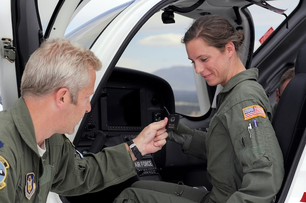 Lt. Col. Scott Oskvarek presents Cadet 1st Class Staci Rouse with a name patch upon her landing to commemorate her historic fight Sept. 7. Rouse was the first cadet in Academy history to fly solo in a powered aircraft. Oskvarek is an instructor pilot with the 70th Flying Training Squadron. (U.S. Air Force photo/Mike Kaplan)