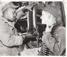 Airman First Class Joseph Godde (left) and Airman Donald Richmond of the 113th Fighter Interceptor Squadron, Indiana Air National Guard, load the .50-caliber machine guns of an F-80 during annual training in 1955.