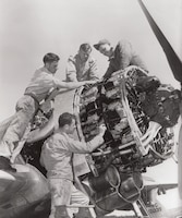 Mechanics of the 118th Fighter Squadron, Connecticut Air National Guard, do engine work on an F-47 at Brainard Field, Hartford Connecticut.