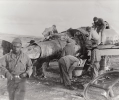 Airmen of the Texas Air National Guard work with a wrecked F-84 fighter, Korea.