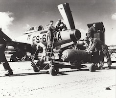 Ground crewmen prepare an F-84 of the 159th Fighter Squadron, Florida Air National Guard, for a combat mission. The unit was deployed to a forward airbase in Korea at the time.