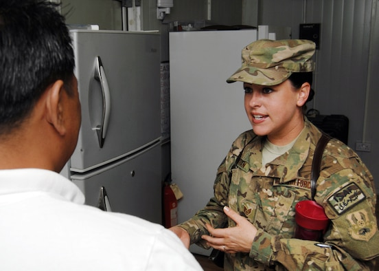 U.S. Air Force Staff Sgt. Jennifer Vaughan, 451st Air Expeditionary Wing public health technician speaks with the manager of a camp that was inspected recently. She offers directions and advice to the managers to bring their kitchen and dining facilities up to standards. (U.S. Air Force photo/Master Sgt. Russell Martin)