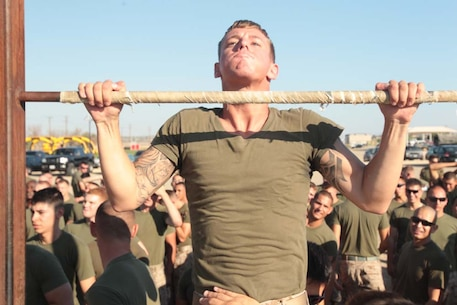 Cpl. Joshua Pacheco, motor transport operator, 1st Tank Battalion, helps the Motor T Team in the pull-ups portion of 1st Tanks' field meet at Del Valle Field Aug. 31, 2012. The Motor T team went on to win the meet for the second time in a row.