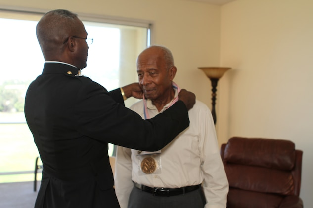 Major General Ronald Bailey, the commanding general of 1st Marine Division awards Lucious Bryant the Congressional Gold Medal during his visit to Bryant?s home here, Sept. 14, 2012. Bryant was drafted to the Marine Corps in 1942 and completed recruit training at Montfort Point becoming one of the 1st African American Marines.