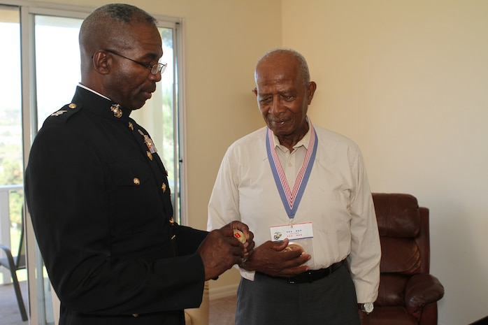 Major General Ronald Bailey, the commanding general of 1st Marine Division gives Lucious Bryant, an 87-year-old native of Carlsbad, Calif., his challenge coin after Bailey presented Bryant with the Congressional Gold Medal, here, Sept. 14, 2012. Bailey said Bryant helped pave the way for African Americans in the Marine Corps.