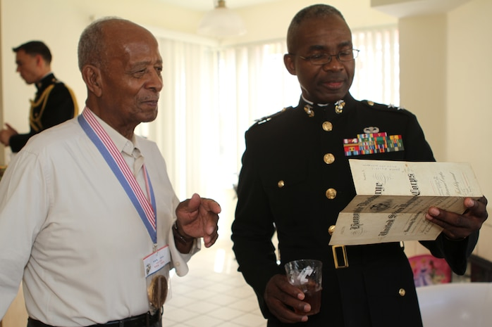 Lucious Bryant, an 87-year-old native of Carlsbad, Calif., and Maj. Gen. Ronald Bailey, the commanding general of 1st Marine Division, look at a pay stub from 1942 and talk about how big a difference it is now, here, Sept. 14, 2012. Bryant was one of the 20,000 African American Marines to graduate recruit training at Montfort Point during a time period when race mattered in the Marine Corps.
