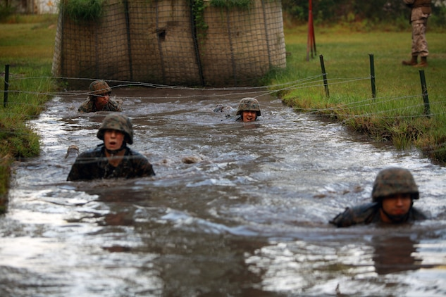 Troops with Landing Support Company, Combat Logistics Regiment 27, 2nd Marine Logistics Group crawl in the water under a barbed wire obstacle during the endurance course at Battle Skills Training School aboard Camp Lejeune, N.C., Sept. 14, 2012. Servicemembers had to cross the muddy water in order to move on to other obstacles and finish the three-mile endurance course.