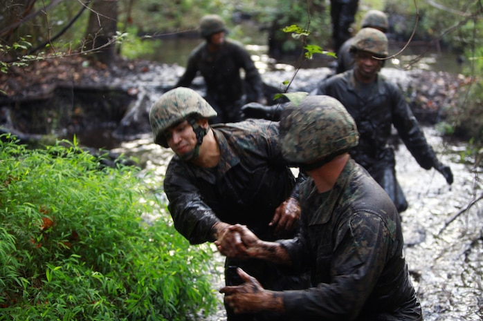 Marines and sailors with Landing Support Company, Combat Logistics Regiment 27, 2nd Marine Logistics Group help each other through the swamp during the endurance course at Battle Skills Training School aboard Camp Lejeune, N.C., Sept. 14, 2012. Servicemembers used teamwork to make sure no Marine was left behind.