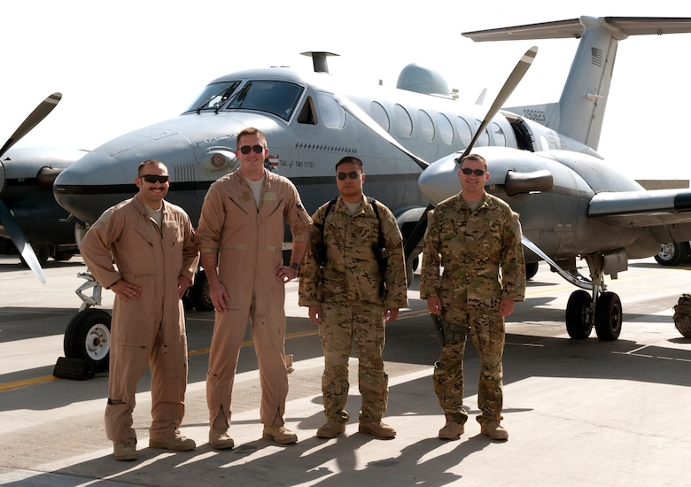 MC-12 Liberty crew members from the 4th Expeditionary Reconnaissance Squadron pause for a photo in front of one of their aircraft at Bagram Airfield, Afghanistan, September 11, 2012. The conclusion of this mission marks a milestone, as it signifies the 4 ERS officially exceeding over 100,000 flying hours using the MC-12s since the unit was stood up in Dec. 2009. 100,000 flying hours roughly equates to 11 and a-half years of flying for one the aircraft. 4 ERS leadership can say they accomplished this feat in under three years using its fleet of MC-12s. (U.S. Air Force photo/1st Lt. Marlene Solano)