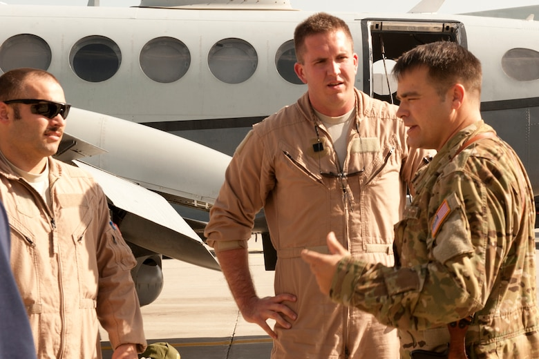 Lt. Col. Jeffrey Alexander (right), Commander 4th Expeditionary Reconnaissance Squadron, talks to crew members of an MC-12 Liberty after returning from a mission at Bagram Airfield, Afghanistan, September 11, 2012. The conclusion of this mission marks a milestone, as it signifies the 4 ERS officially exceeding over 100,000 flying hours using the MC-12s since the unit was stood up in Dec. 2009. 100,000 flying hours roughly equates to 11 and a-half years of flying for one the aircraft. 4 ERS leadership can say they accomplished this feat in under three years using its fleet of MC-12s. (U.S. Air Force photo/1st Lt. Marlene Solano)