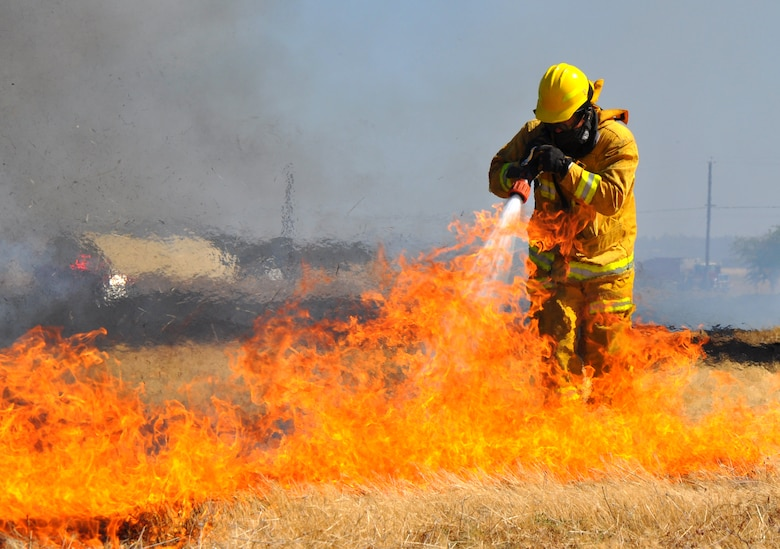 A U.S. Air Force firefighter extinguishes flames from a grass fire at Beale Air Force Base, Calif., Sept. 13, 2012. Beale firemen wear protective suites to shield them from heat. (U.S. Air Force photo by Staff Sgt. Robert M. Trujillo/Released)