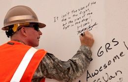 "Maj. Gen. Merdith W.B. ""Bo"" Temple, former deputy commander of the U.S. Army Corps of Engineers, signs a protective wall with a personal motto at the Corps' Gulf Region South compound near Basra, Iraq, in October 2009.  Temple retired from the U.S. Army Aug. 31, 2012.  (U.S. Army Corps of Engineers Photo)"