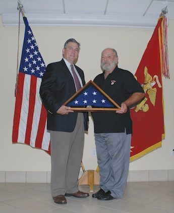 """Mike Williamson, left, director, Logistics Services Management Center, Marine Corps Logistics Command, presents Richard """"Rich"""" Zupko's logistics management specialist, LSMC, Command, Control, Communications, Computers and Intelligence Systems Division, MCLC, with an American flag during his retirement ceremony, Aug 21."""
