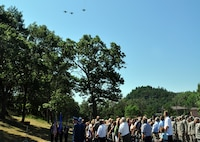 """Family members and guests watch a """"missing man formation"""" fly-over at Volk Field during a July 11 memorial service for the base's namesake, 1st Lt. Jerome Volk, the first Wisconsin Air National Guard pilot to die in the line of duty during the Korean conflict. Volk was shot down during a combat sortie against communist forces Nov. 7, 1951, and his remains have never been recovered. In 1957 the Wisconsin legislature renamed the portion of Camp Williams used by the Wisconsin Air National Guard as Volk Field. Don Volk, 1st Lt. Volk's younger brother and next of kin, and dozens of other relatives attended the ceremony, which included full military honors. Wisconsin National Guard photo by 1st Sgt. Vaughn R. Larson"""