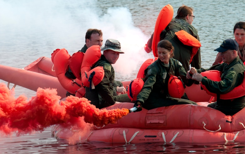 Airmen of the 133rd Airlift Wing are taking part in survival, evasion, resistance, and escape (SERE) training and water survival training including: lift raft familiarization, parachute disentanglement and rescue techniques.at the Army Training Site Arden Hills, Minnesota Sept. 16, 2012. Here a group of Airmen practice water survival while lighting both signal flares and smoke flares. U.S. Air Force photo by Tech. Sgt. Erik Gudmundson/released