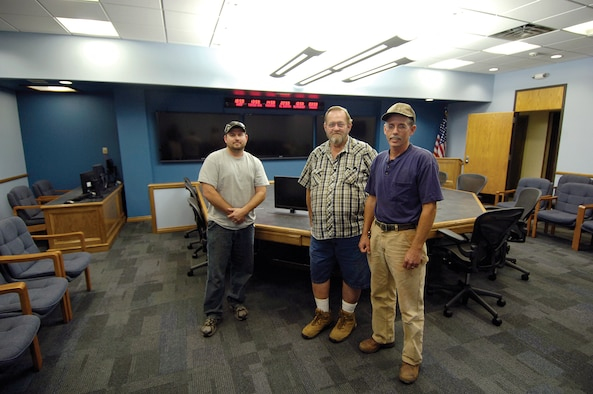 Members of the 552nd Eagle Team stand in the 552nd Battle Cab war room they gutted then rebuilt into a modern, spacious environment for senior leadership to work during emergencies or exercises.  Aaron Price, Chuck Stevens and Chris Coffman, from left, plus Hunter Stanbaugh, not pictured, transformed the area with pop-up computers in a new  hand-built central table,  a raised ceiling, non-glare lighting and more room for a gallery row that before made a tight squeeze for those seated at the table.  (Air Force photo by Margo Wright)