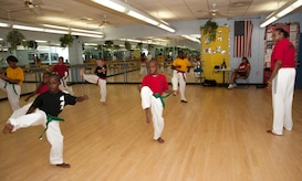 "Master Lynnette Love observes her students as they perform a kata form during a scheduled class at the Love Academy at Andrews Youth Center on Aug. 14, 2012..  Love is an Olympic taekwando champion, and her story has inspired a movie called ""Seoul, U.S.A.,"" which is being produced later this year.  (Photo/Bobby Jones)"