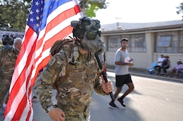 A Marine Special Operations Command (MARSOC) Marine runs bearing the American Flag, during the Heartbreak Ridge Half Marathon at Camp Pendleton's 43 Area Parade Deck, Sept. 8.
