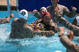 A player attempts to keep possession of a water polo ball while defenders begin swarm around him during a combat water polo tournament at Camp Pendleton's 13 Area Pool, Sept. 12. Marine Corps Community Services' Pendleton Cup Series provided Marines and sailors with an opportunity to build unit cohesion and camaraderie while competing for monetary prizes that will be awarded to their respective units.