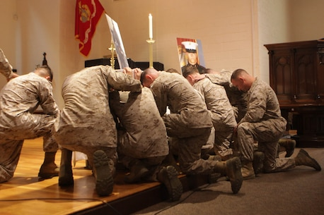Marines with 2nd Law Enforcment Battalion huddle together in silence in rememberance of Sgt. Joshua Ashley during a memorial ceremony at the Protestant chapel aboard Marine Corps Base Camp Lejeune Sept. 12.  Ashley, a military dog handler, was killed in Afghanistan in July while conducting operations in Helmand province. (Photo by Sgt. Bobby J. Yarbrough)