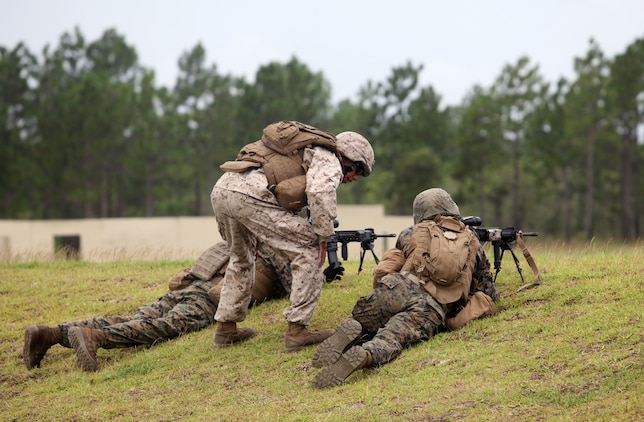 An instructor gives advice to fellow Marines with 1st Battalion, 6th Marine Regiment, 2nd Marine Division, as they provide suppressive fire during a training exercise as part of the Forge Academy Sept. 18. The Forge Academy is an approximately four-week long course designed to improve the proficiency of 1/6?s fireteam leaders. Throughout the course, the students were educated on troop welfare, the psychological and physiological effects of combat, infantry tactics and the responsibilities of being a fireteam leader.