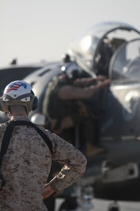A Marine ground crewman supervises the tarmac as a pilot of an AV-8B Harrier II Plus exits his cockpit, Sept. 18. The Marines are a part of Marine Attack Squadron 211, 3rd Marine Aircraft Wing (Forward). The squadron supports troops on the ground with air support and reconnaissance operations.