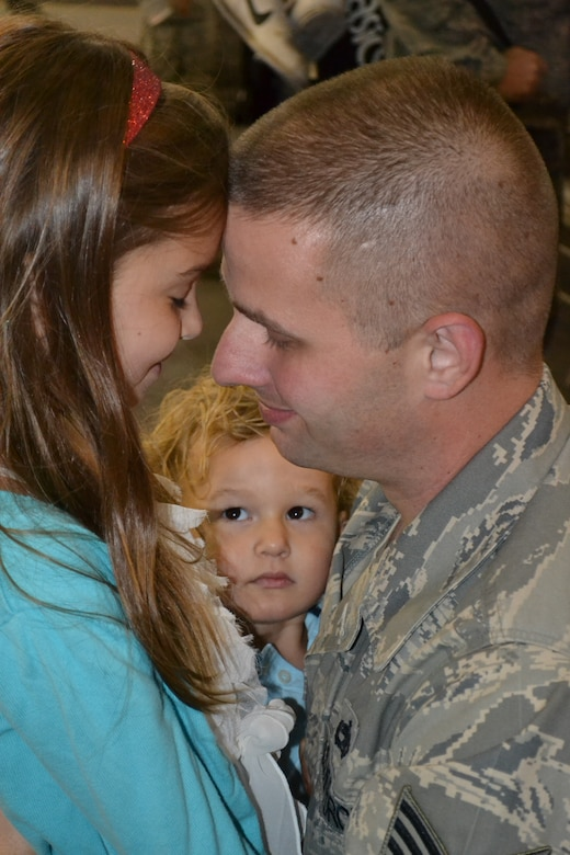 Tech. Sgt. Ron Roe shares an intimate moment with his daughter, Krysta, shortly after arriving back home at Tinker Air Force Base on Monday, Sept. 10, following a six-month deployment to Southwest Asia, while his son, William, looks on. Sergeant Roe was one of approximately 50 Airmen from the 552nd Air Control Wing to have returned from the recent deployment to Al Dhafra Air Base, United Arab Emirates, in support of ongoing operations in Afghanistan. (Air Force photo by Darren D. Heusel)