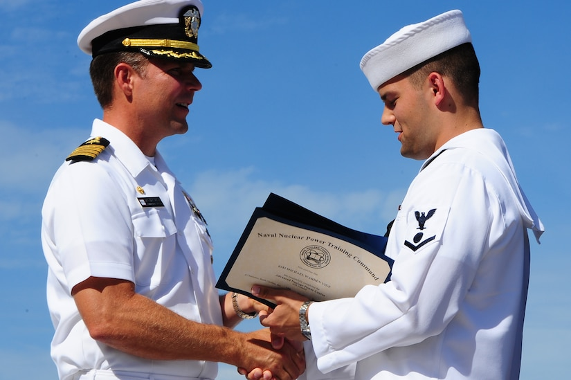 Petty Officer 3rd Class Michael Vige receives the Class Honorman award for Enlisted Class 1203 from Capt. Jon Fahs, Naval Nuclear Power Training Command commanding officer, during the NNPTC graduation ceremony Sept. 14, 2012, at Joint Base Charleston - Weapons Station, S.C. The Honorman award is given to the Sailor with the highest grade point average. Vige's grade point average was 3.96. (U.S. Air Force photo/ Airman 1st Class Chacarra Walker)