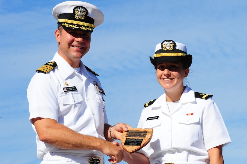 Ensign Donna Purviance receives the Vice Admiral Behrens award for Officer Class 1203 from Capt. Jon Fahs, Naval Nuclear Power Training Command commanding officer, during the NNPTC graduation ceremony Sept 14, 2012, at Joint Base Charleston - Weapons Station, S.C. The Behrens award is given to the officer with the highest grade point average. Purviance's grade point average was 3.79. (U.S. Air Force photo/ Airman 1st Class Chacarra Walker)