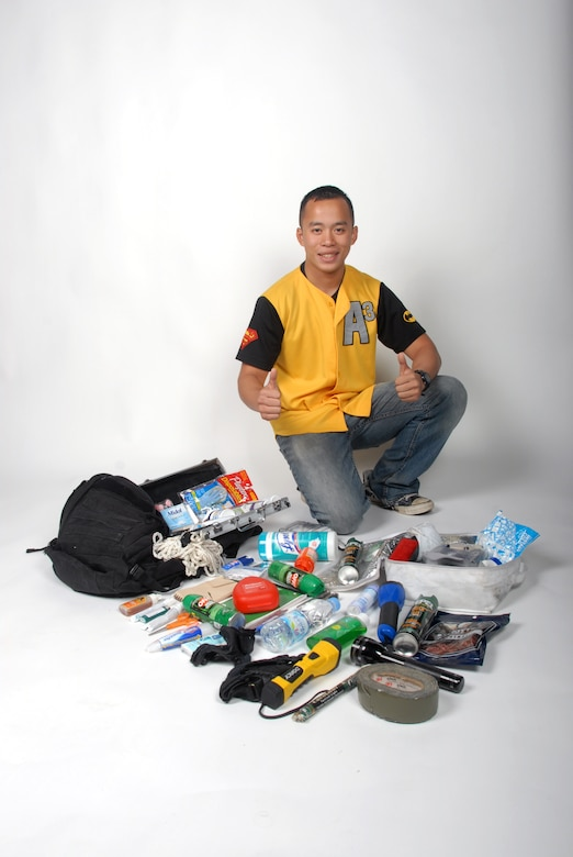 Senior Airman Charles Sothikhoun, 8th Maintenance Squadron nondestructive inspector, poses with all the supplies he hauls around in his backpack at Kunsan Air Base, Republic of Korea, Sept. 13, 2012. He said his goal in helping people is so no one gets in trouble, is forgotten or left alone. (U.S. Air Force photo/Staff Sgt. Jonathan Fowler)