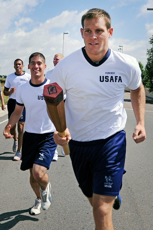 Cadet 1st Class Connor Ference of Cadet Squadron 10 takes the baton to start his leg of five runners during the combined 9/11-POW/MIA Remembrance Run as it exits Peterson Air Force Base, Colo., Sept. 13, 2012. The run ended at the Academy Terrazzo after 45 teams of five traversed the 45-mile journey past various locations in Colorado Springs. The end of the remembrance run signified the start of a 39-hour vigil run on the Terrazzo, commemorating 39 years since Operation Homecoming, the repatriation of POWs from the Vietnam War. (U.S. Air Force photo/Mike Kaplan)
