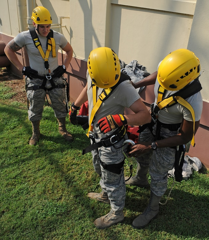 Cable Dawgs from the 2nd Communications Squadron check each other's safety harnesses on Barksdale Air Force Base, La., Sept. 18. The Airmen donned the harnesses so they could climb a tower to inspect antennas. In addition to safety harnesses, Cable Dawgs wear helmets, gloves and special boots to assist them in climbing. (U.S. Air Force photo/Senior Airman Micaiah Anthony)(RELEASED)