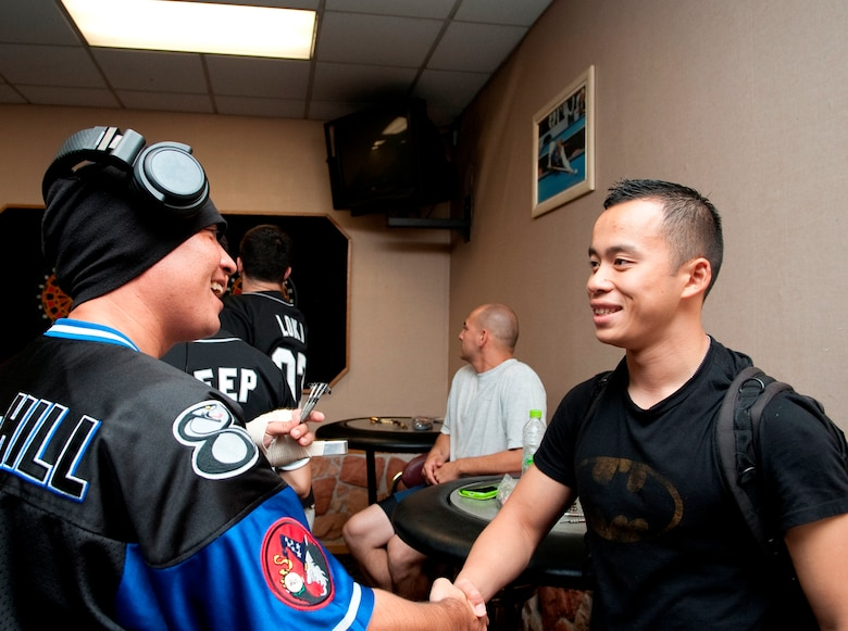 Senior Airman Charles Sothikhoun, right, makes his daily rounds with his backpack at Kunsan Air Base, Republic of Korea, Sept. 20, 2012. Dubbed as Kunsan's unofficial Wingman, he said his goal in helping people is to make sure nobody gets in trouble, is forgotten or left alone. (U.S. Air Force photo/Senior Airman Brigitte N. Brantley)
