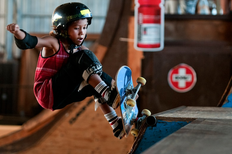 "Kai ""Kai Boy"" Martin, 7, shows off his skateboarding skills during a skate lesson at the Hickam Skate Hangar, Joint Base Pearl Harbor-Hickam, Hawaii. The converted hangar is the only indoor wooden facility on all the Hawaiian Islands. It also boasts the only wooden keyhole bowls, or empty swimming pool shaped ramps, on Oahu. In addition, it has a 15,000 square foot street course, multiple mini ramps, 12-foot vertical ramp with a 14-foot tombstone connected to a saddle and three-quarter pipe. (U.S. Air Force photo/Staff Sgt. Mike Meares)"