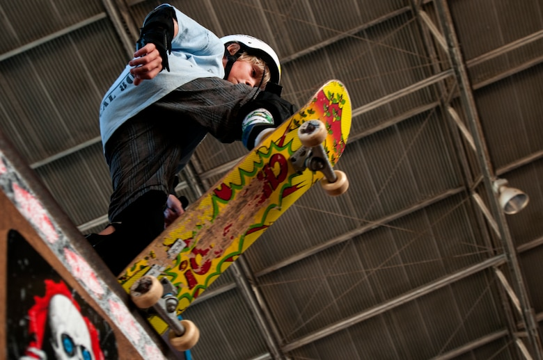 A young skater drops in on the quarter-pipe ramp during a skate lesson at the Hickam Skate Hangar, Joint Base Pearl Harbor-Hickam, Hawaii. The converted hangar is the only indoor wooden facility on all the Hawaiian Islands. It also boasts the only wooden keyhole bowls, or empty swimming pool shaped ramps, on Oahu. In addition, it has a 15,000 square foot street course, multiple mini ramps, 12-foot vertical ramp with a 14-foot tombstone connected to a saddle and three-quarter pipe. (U.S. Air Force photo/Staff Sgt. Mike Meares)