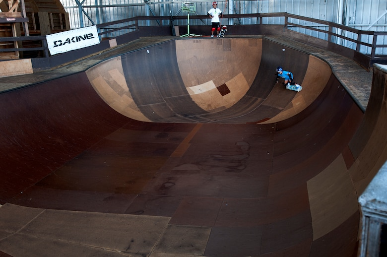 Kody Tamanaha, 8, of Mililani, Hawaii, skates inside a bowl while her brother, Ian, 10, waits his turns at the Hickam Skate Hangar Aug. 16 at Joint Base Pearl Harbor-Hickam, Hawaii. The converted hangar is the only indoor wooden facility on all the Hawaiian Islands. It also boasts the only wooden keyhole bowls, or empty swimming pool shaped ramps, on Oahu. In addition, it has a 15,000 square foot street course, multiple mini ramps, 12-foot vertical ramp with a 14-foot tombstone connected to a saddle and three-quarter pipe. (U.S. Air Force photo/Staff Sgt. Mike Meares)