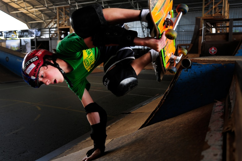 Seth Lefferts, 13, son of Tech Sgt. Chad Lefferts, Pacific Air Forces Headquarters, performs a trick on his skateboard at the Hickam Skate Hangar Aug. 21 at Joint Base Pearl Harbor-Hickam, Hawaii. The converted hangar is the only indoor wooden facility on all the Hawaiian Islands. It also boasts the only wooden keyhole bowls, or empty swimming pool shaped ramps, on Oahu. In addition, it has a 15,000 square foot street course, multiple mini ramps, 12-foot vertical ramp with a 14-foot tombstone connected to a saddle and three-quarter pipe. (U.S. Air Force photo/Staff Sgt. Mike Meares)
