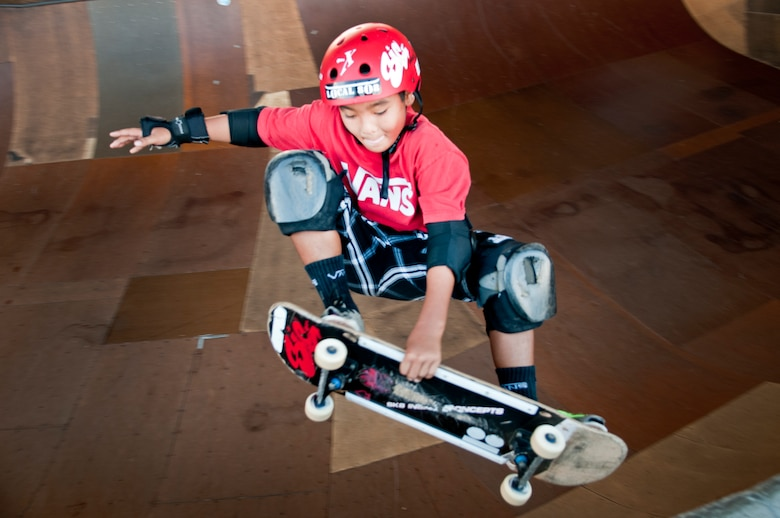 Ian Tamanaha, 10, of Mililani, Hawaii, performs a trick while skating one of the bowls at the Hickam Skate Hangar Aug. 16 at Joint Base Pearl Harbor-Hickam, Hawaii. The converted hangar is the only indoor wooden facility on all the Hawaiian Islands. It also boasts the only wooden keyhole bowls, or empty swimming pool shaped ramps, on Oahu. In addition, it has a 15,000 square foot street course, multiple mini ramps, 12-foot vertical ramp with a 14-foot tombstone connected to a saddle and three-quarter pipe. (U.S. Air Force photo/Staff Sgt. Mike Meares)