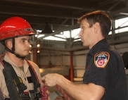 """Randall's Island, NEW YORK – A firefighter and instructor with the New York City Fire Department explains to Sergeant Daniel Barbadillo, an extraction Marine with Initial Response Force """"B,"""" how he will repel down two stories to rescue a """"stranded victim"""" from a ledge and get them safely to the ground. The FDNY has been involved in training the Mariens and sailors of CBIRF since 1997, when Chief Raymond Downey helped expand CBIRF's technical rescue platform."""