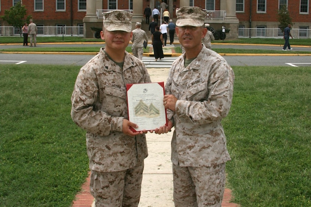 Colonel Andy Bianca (right), Marine Corps Systems Command's Program Manager for Infantry Weapon Systems, presents Corporal Andres Medina with his promotion warrant in early September