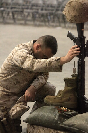 A Marine pays his final respects to Sgt. Bradley Atwell during a memorial ceremony, Sept. 20. During the ceremony, Marines paid tribute to Atwell, an aircraft electrical, instrument and flight control systems technician with Marine Aviation Logistics Squadron 16, from Kokomo, Ind. Atwell was killed in action while engaging insurgents during an attack on Camp Bastion, Sept. 14.