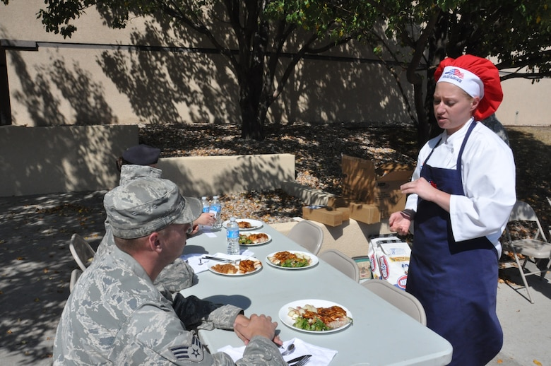 Senior Airman Evelyn Widomski, 321st Missile Squadron chef, presents her dish composed of a homemade chicken barbecue, jalapeno poppers, a summer salad and red potatoes cooked with rosemary and butter to the judges of the 90th Operations Group Top Chef competition Sept. 18. Widomski's dish earned her first place and gift certificates totaling $100 for the commissary. (U.S. Air Force photo by Senior Airman Jennifer Dowling, 90th Missile Wing command chief executive)
