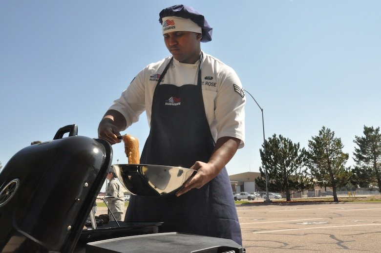 Senior Airman Jamall St. Rose, 320th Missile Squadron chef, places chicken on the grill during the 90th Operations Group Top chef competition Sept. 18. (U.S. Air Force photo by Senior Airman Mike Tryon)