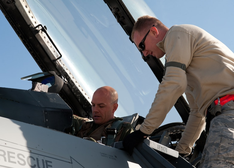 Tech. Sgt.  Christopher Thesenvitz, 175th Fighter Squadron crew chief, assists Capt. Travis Barnett, 175th FS F-16 pilot, in checking his gear prior to engine start during the South Dakota Air National Guard's 2012 Live Drop exercise at Ellsworth Air Force Base, S.D., Sept. 19, 2012. The F-16 is highly maneuverable and has proven itself both in air-to-air combat and air-to-surface operations. (U.S Air Force photo by Airman 1st Class Alystria Maurer/Released)