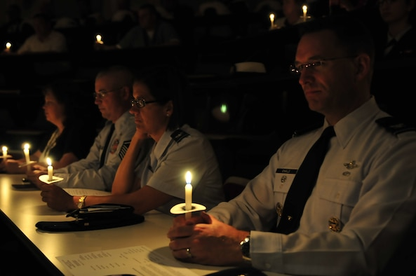 Col. Thomas Engle, vice commander for the 552nd Air Control Wing, right, Col. Stella Smith, 552nd Maintenance Group commander, and Master Sgt. Tom McManus, 964th Airborne Air Control Squadron first sergeant, participate in a candlelight vigil honoring fallen service members during a POW/MIA recognition ceremony Sept. 12 at the VA Medical Center in Oklahoma City. (Air Force photo by Darren D. Heusel)