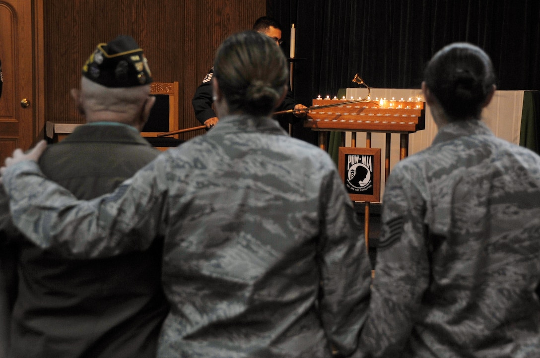 Tech. Sgt. Autum Curran and Tech. Sgt. Crystal Lundell, members of the 51st Logistics Readiness Squadron, provide comfort to a veteran at a Prisoner Of War/Missing In Action candlelight vigil at the Osan Air Base chapel, Republic of Korea, Sept. 19, 2012. Osan held several events, to include a 24-hour run and retreat ceremony, to commemorate POW/MIA week. (U.S. Air Force photo/Staff Sgt. Craig Cisek)