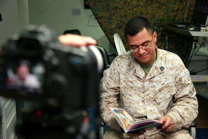 Gunnery Sgt. Rodolfo Gonzalez, disbursing chief, 15th Marine Expeditionary Unit, reads a book in his office, on the USS Peleliu, Sept. 22. The United Through Reading program helps connect servicemembers to their family members by providing them the opportunity to record themselves reading a book to their loved ones. The recordings can be up to 30 minutes long. If the servicemembers brought the book with them, they can mail the book with the recording back home. If they didn?t bring books, they can borrow one from the unit.