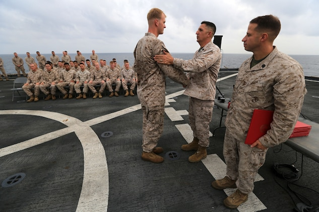 Cpl. Joshua Brooks, a Petoskey, Mich., native and machine gun section leader with Charlie Company, Battalion Landing Team 1st Battalion, 2nd Marine Regiment, 24th Marine Expeditionary Unit, receives his diploma during a Corporal's Course graduation ceremony aboard the USS Gunston Hall in the Gulf of Aden, Sept. 22. Brooks was the honor graduate of the course, which took place both ashore in Kuwait and aboard the ship. The 24th MEU is deployed with the Iwo Jima Amphibious Ready Group as a theater reserve force for U.S. Central Command and is providing support for maritime security operations and theater security cooperation efforts in the U.S. Navy's 5th Fleet area of responsibility.