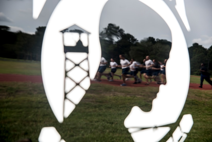 Airmen are seen running in a reflection of a Prisoner of War/Missing in Action emblem painted on the door of a car during the POW/MIA Run Sept. 20, 2012, at Joint Base Charleston – Air Base, S.C. Different units from the joint base carried the flag for 30 minutes each from 3:30 p.m. Sept. 20 to 3:30 p.m. Sept. 21 in honor of all POW's and MIA's. (U.S. Air Force photo/Staff Sgt. Rasheen Douglas)